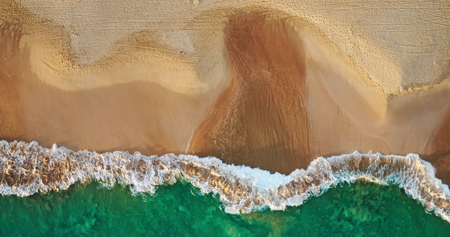 Aerial view waves break on white sand beach at sunset, land meets sea