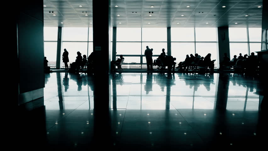 Travelers expecting plane in airport waiting hall, people walking with suitcases