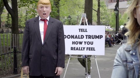 """NEW YORK - MAY 15, 2016: """"tell Donald Trump how you really feel"""" sign with masked impersonator in Park in NYC. Washington Square Park is the scene of much street art and performance in the city."""