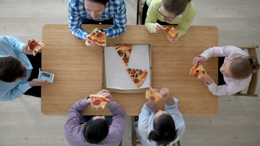 Group of diverse people eating pizza sitting around the table | Shutterstock HD Video #16933153