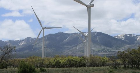 MONTICELLO, UTAH - MAY 2016: Windmill farm rural mountain valley. Wind farm southern. Scenic mountain. Source of renewable energy wind turbines. Blades pointed into wind by computer controlled motors.