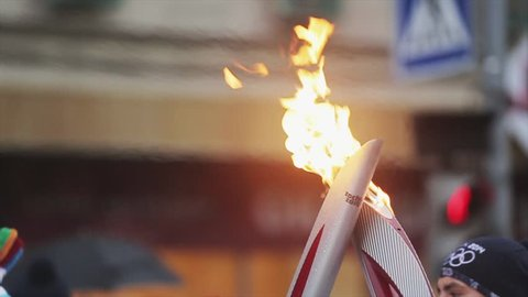 SAINT PETERSBURG, RUSSIA - OCTOBER 27, 2013: Relay race Sochi Olympic torch in Saint Petersburg in October 2013. Two burning torch. Passing flame by torchbearers. Slow motion. Close up