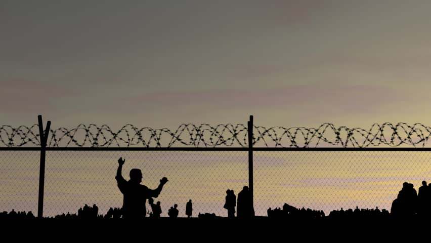 Refugees. Silhouettes of people at sunset, fence with barbed wire and iron bars! People go to the border | Shutterstock HD Video #16963783