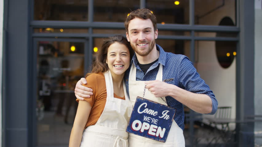 4K Happy owners outside cafe hold up a sign to show they are open for business. UK - April, 2016