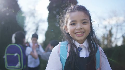 4K Portrait of smiling little girl with backpack, outdoors in school playground UK - April, 2016