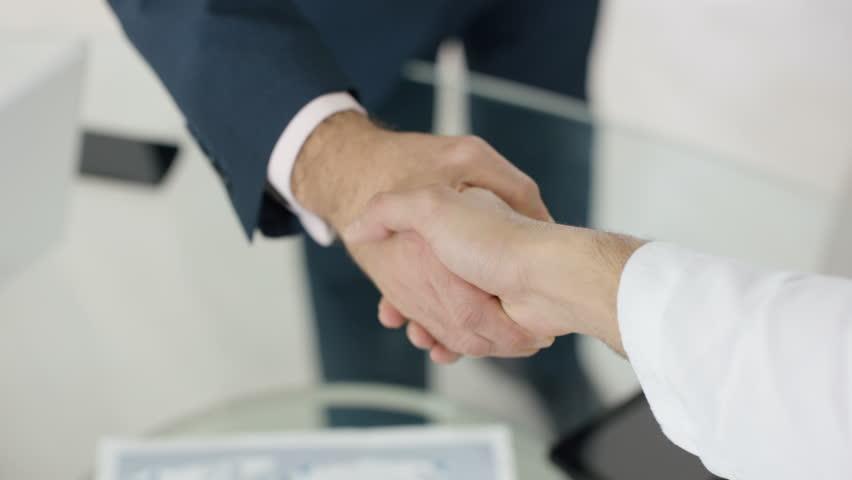 4K Close up on hands unrecognizable Arabic & businessmen shake hands on a deal. Shot on RED Epic. UK - April, 2016