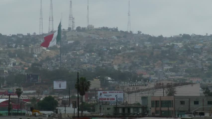 the Mexican flag is seen waving above downtown Tijuana Mexico.