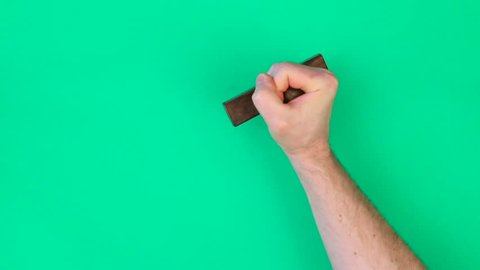 Adult male hand stamping blank green background with a rubber stamp