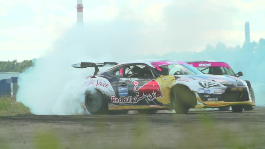 MOSCOW, RUSSIA - MAY 15, 2016 : Slow motion shot of cars drifting with lots of smoke during drift competition in Moscow, Russia on a sunny summer day.