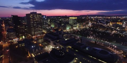 Aerial static establishing view of the city of Ottawa at night sunset downtown with cars passing by