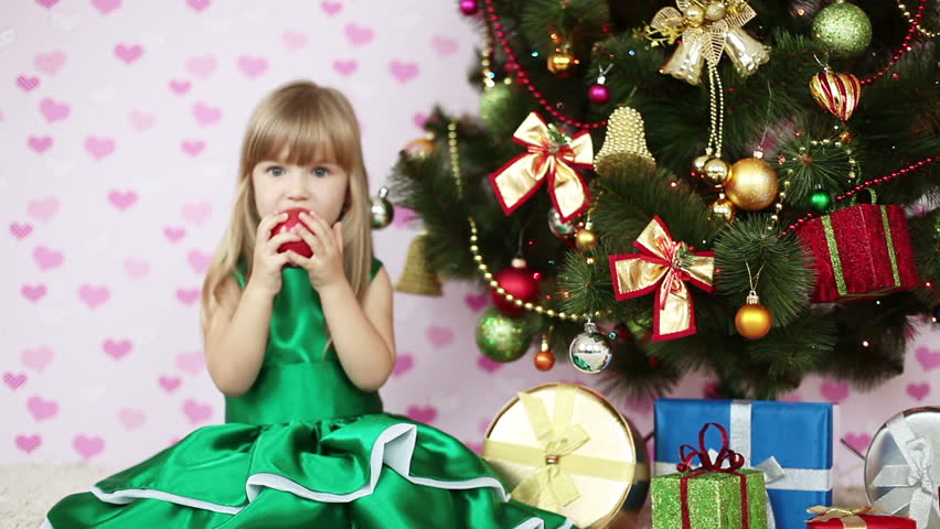 Girl eating an apple near a Christmas tree. She sits on the floor
