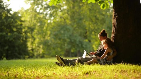 Young mother and her daughter playing on a tablet and a dog in a beautiful park