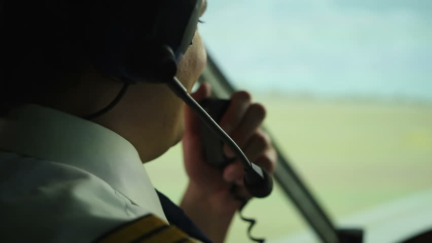 Happy pilot talking to controller, navigating airliner while moving on runway. Male aviator requesting permission from dispatcher for taking off radio, airport traffic controlling system, crew member