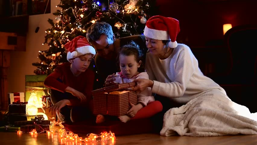 Christmas night, a cheerful family of four people at the foot of the Christmas tree, the little girl finds a teddy bear in her gift box, mom and the little boy wear a santa claus hat