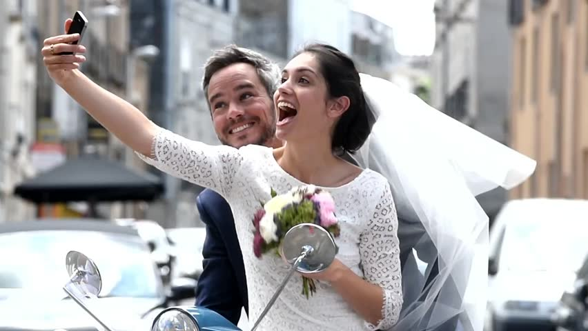 Cheerful newlywed couple having fun on a scooter, they are making selfies with a smartphone before to leave for their honeymoon