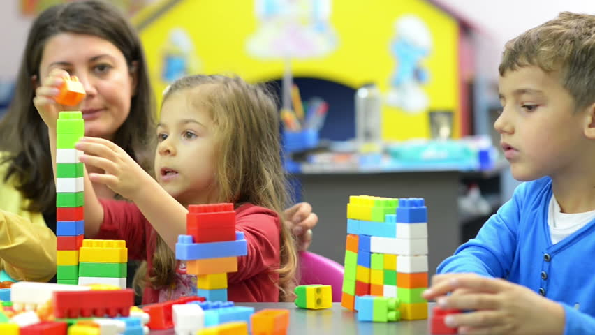 Kids and educator playing with plastic building blocks at kindergarten