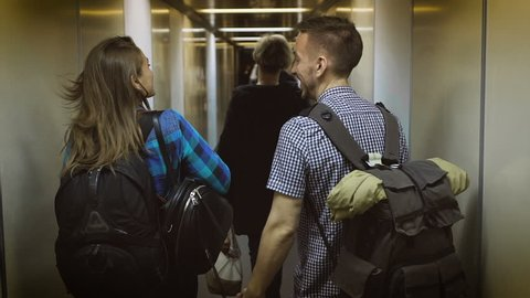 Man and woman at the airport, go down the hall to their seats on the plane.