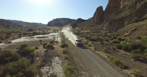 Aerial scene of car traveling on dirt road a dry, rocky, landscape. Monumental scenery. Car leves dust while driving. Fast scene. Canyon of Piedra Parada, Chubut, Patagonia Argentina. Hiking place.