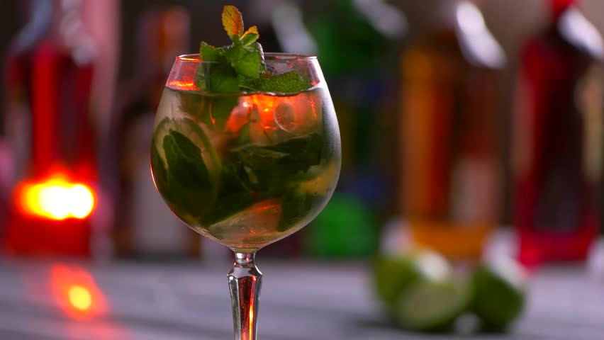 Glass of beverage is rotating. Coktail with mint and lime. Chilled alcohol drink. Try the hugo cocktail.