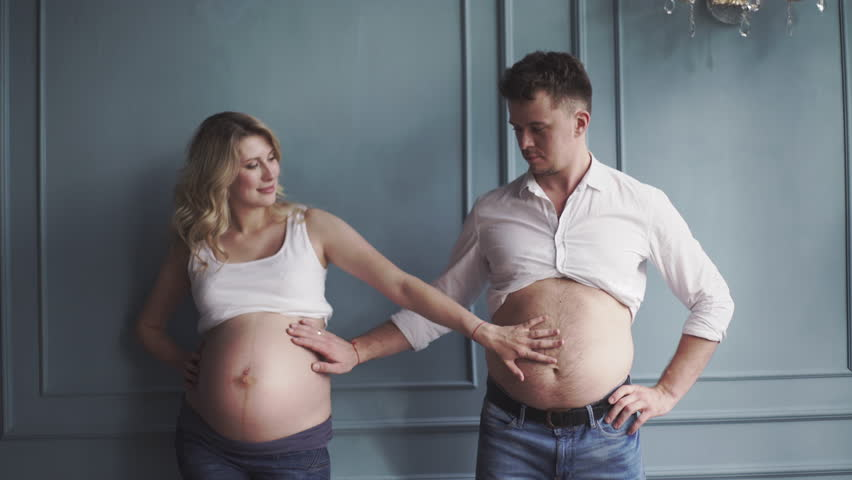 Pregnant couple near the wall. Pregnant woman and pregnant man