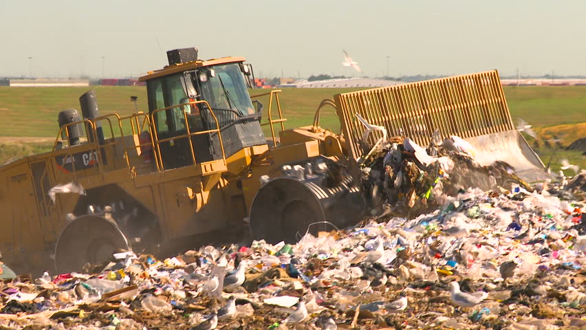 CALGARY, CANADA - JULY 17, 2010: Tractors move garbage at the garbage dump on July 16, 2010 in Calgary, Canada