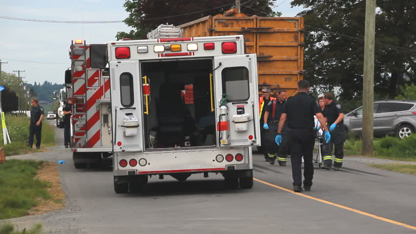 MISSION, BC/CANADA â?? MAY 14 2016: A driver is transported to an ambulance after a serious car accident when a large commercial truck broadsided a car attempting to turn into a side street.