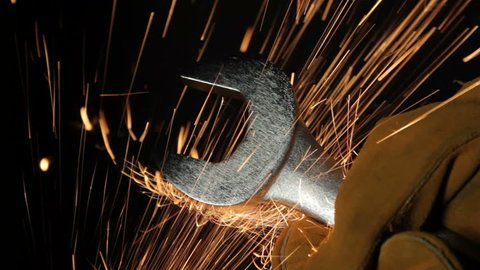 Sparks fly past a wrench held in a workers' hand
