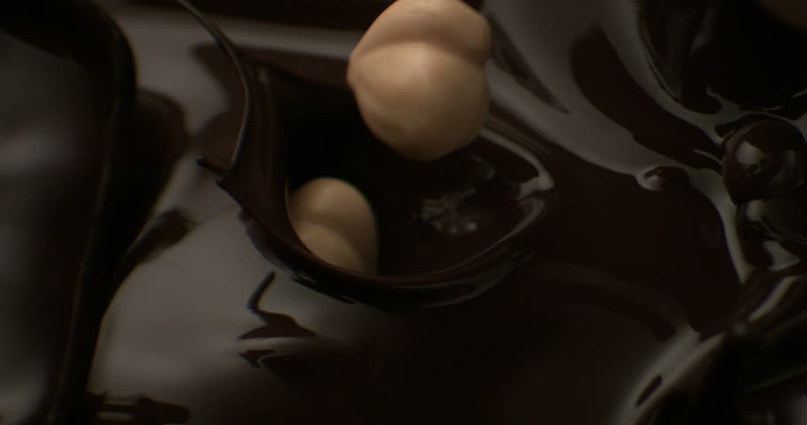 hazelnuts fall in chocolate fondant and liquid milk in slow motion
