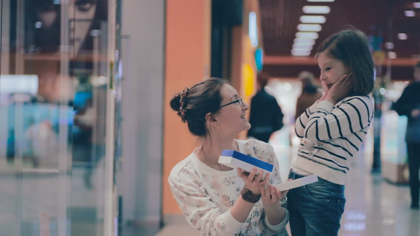 Mother shows daughter a gift box just baught at mall. Being excited about shopping sales. | Shutterstock HD Video #17365423