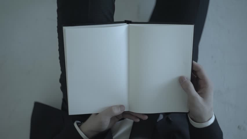 Slow motion shot of a businessman holding a notebook with blank white pages and turns the page
