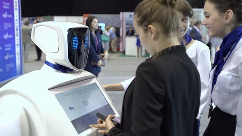 Novosibirsk Russia - June 9 2016: Robot with interactive display communicates with visitors in a business centre. People using his touch screen. High tech system today. Innovative assistant in society