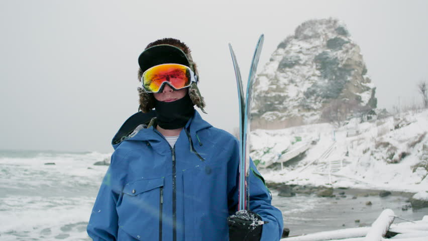 Skier Profile Portrait Holding Skis Wearing Goggles Hat, Jacket, Winter Gear. Looking at Camera Snowy Landscape Mountain Rock, Ocean Waves, Snow Background. #17405143