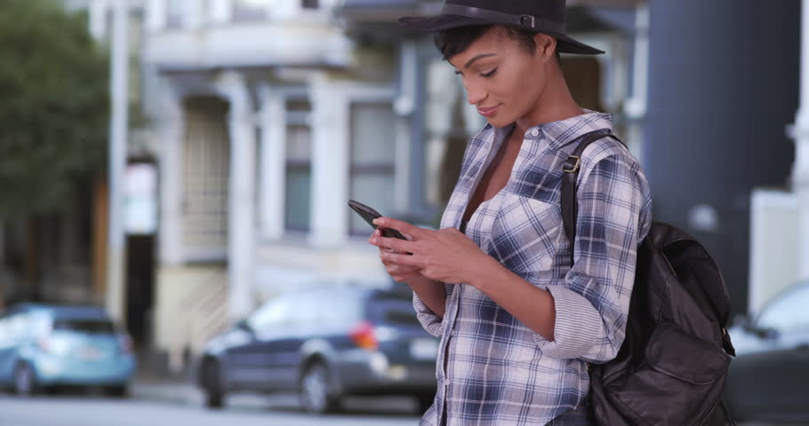 Pretty Hipster woman texting on cell phone in San Francisco using smartphone sms app. Happy Black woman in her 20s. | Shutterstock HD Video #17405173