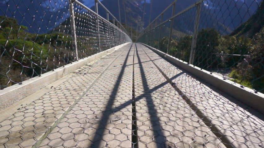 View Of Hiker's Feet Walking On Suspension Bridge At Hooker Valley Track, Mount Cook National Park, New Zealand. Camera Motion From Low Angle Sliding Upwards