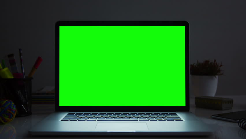 Laptop with green screen. Dark office. Dolly in. Perfect to put your own image or video. Track with perspective corner pin.