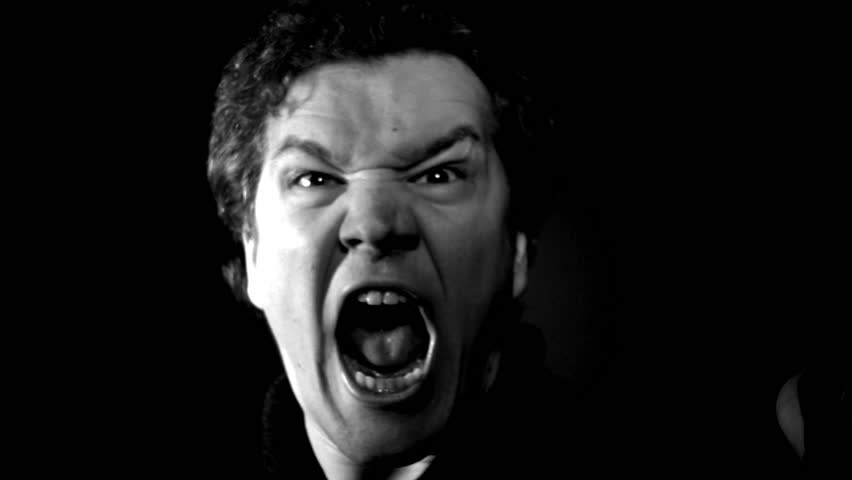 Furious yelling man in slow motion. This guy is so angry he's making an evil screaming rage face. Raging and livid, man moves in close with serious expression. #17428756