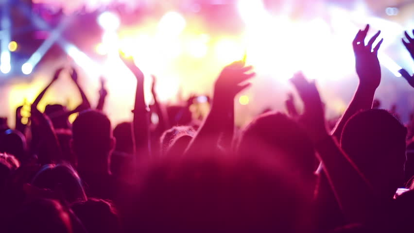 Iconic night rock concert front row crowd cheering slomo 50p.Slow motion shots from a night rock concert.People cheer move lift and clap their hands in unison against the strobing stage lights.
