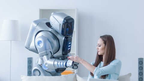 Pleasant robot giving glass of water to a woman