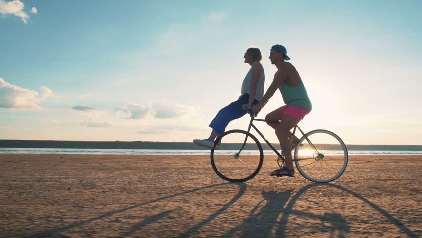 Young woman and man riding a bicycle at the shore and having some fun, slow motion