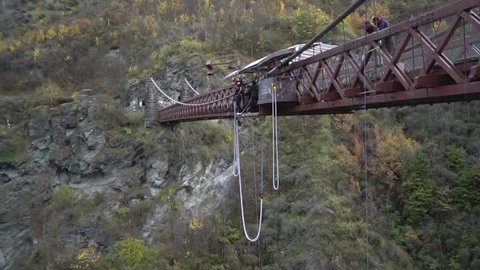 QUEENSTOWN, NEW ZEALAND -CIRCA 2016: Slow motion shot of Couple tourists bungy jumping from the Kawarau Gorge Suspension Bridge into Kawarau river. Commercial Bungy Jumping was born here in 1988.