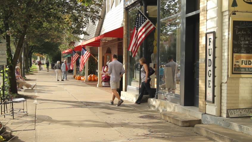 COOPERSTOWN, NY - SEPT 24, 2011: People stroll down the sidewalk of the main street on September 24, 2011 in Cooperstown.