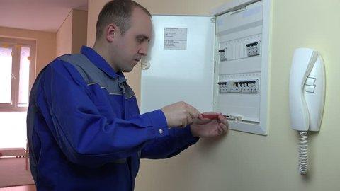 Man in blue uniform working on a circuit breaker at flat house. Static closeup shot.