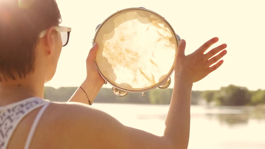 Musical instrument tambourine or pandeiro on a background of the sky at sunset