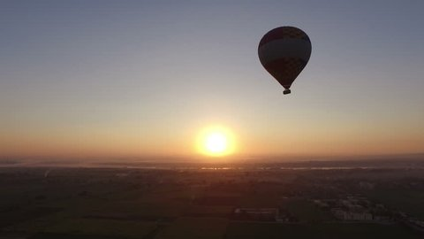 Hot air balloon flying over the fields in Luxor at beautiful sunrise