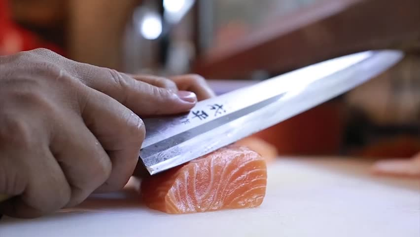 Sushi Chef Slices fresh Salmon on the sushi bar.  A sushi-man slicing a salmon steak with his Japanese knife. Preparing sushi nigiri fish. Japanese cuisine recipes. | Shutterstock HD Video #17494693