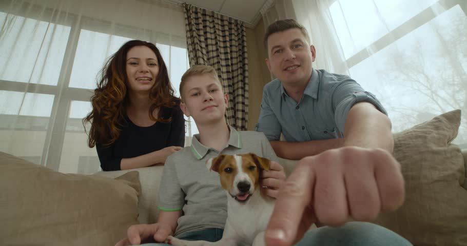 POV, close-knit happy family with a dog the Jack Russell Terrier talking to relatives on Skype