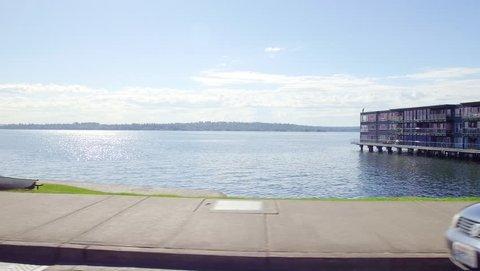 Kirkland, Lake Washington - David E. Brink Waterfront Park Pan Shot. Green Grass and Blue Water on a Sunny Summer Day. Gimbal Driving Shot.