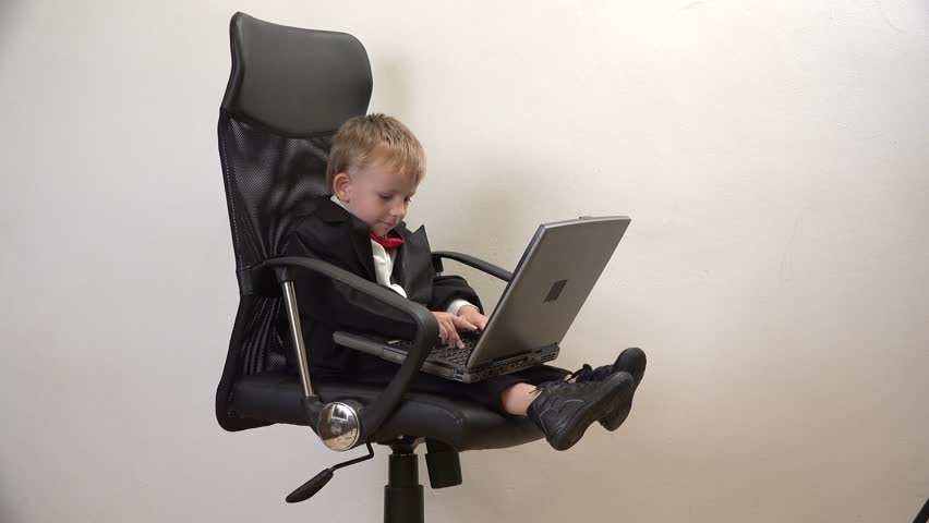 Little Cute Child Rotating In An Office Chair Businessman Has Fun