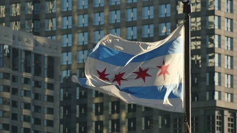 . Flagstaff on the Golden Mile in Chicago city center. Chicago flag waving in the Windy City of Chicago. Flag with the skyscrapers glass windows background.