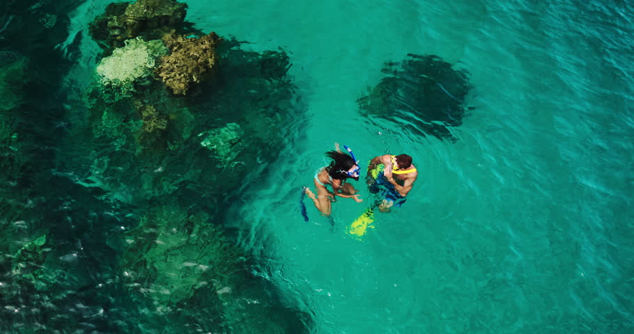 Aerial view young couple snorkeling in tropical blue ocean